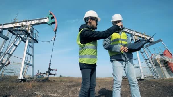 Inženýři pracující poblíž sloupové jeřáby ropa, ropné plošiny. Ropné produkce průmyslu koncept.