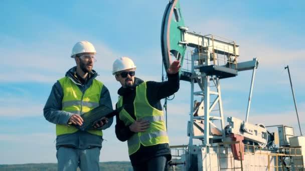 Muži v uniformě pracuje na pole poblíž věže. Koncept průmyslu ropy.
