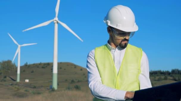 Inženýr je v provozu notebooku před větrných mlýnů. Čisté, eko šetrné energetické koncepce.