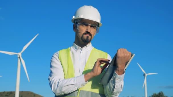 Mužské pracovník pracuje tablet stoje vedle turbíny věže. 4k