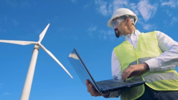 Mužské inženýr typy na svém notebooku, stojící poblíž elektrický větrné turbíny. 4k.