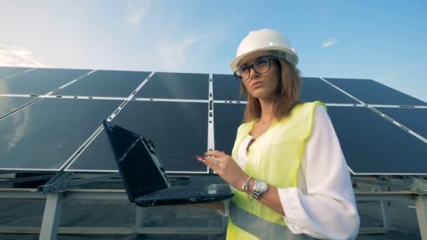 Specialista na solární energii je pěší podél konstrukce baterie s její laptop