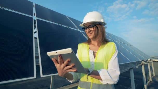 Stojí vedle solární modul s úsměvem a pracuje její počítač energetika inženýr