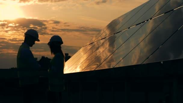 Solární panely a dva pracovníci siluety mluví.