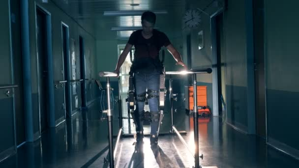 A man walks on a track, using robotic orthopaedic device at a clinic. 4K