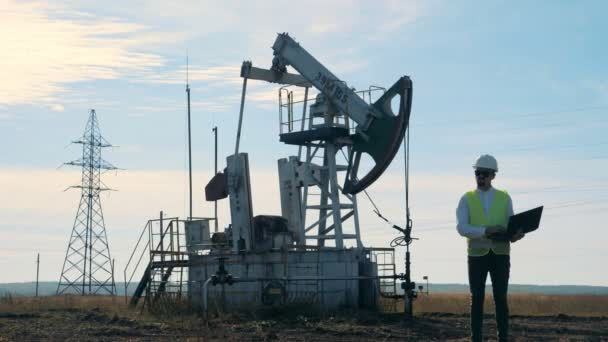 Oil-derrick and a male specialist operating his laptop beside it