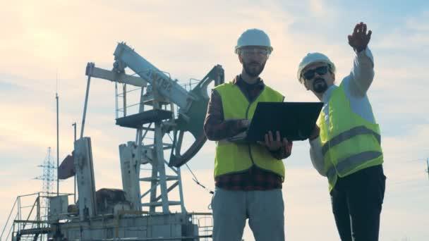 Ein Energetik-Experte gibt einem anderen Anweisungen, während er in der Ölförderstätte ist. Ölindustrie, Ölindustrie, Konzept des Ölsektors.