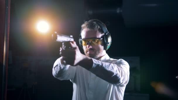 Egy ember egy pisztolyt célja a lőtéren, közelről.