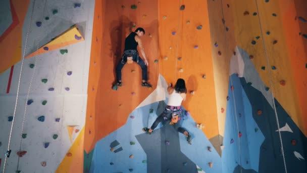 Egy férfi egy nőt, hogy a falon mászni, közelről segít.