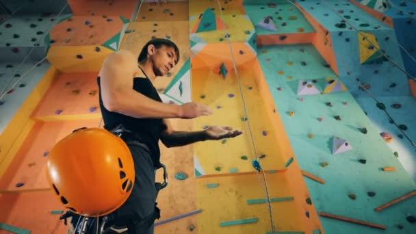 Muž s horolezecké vybavení stojí u zdi, zblízka.