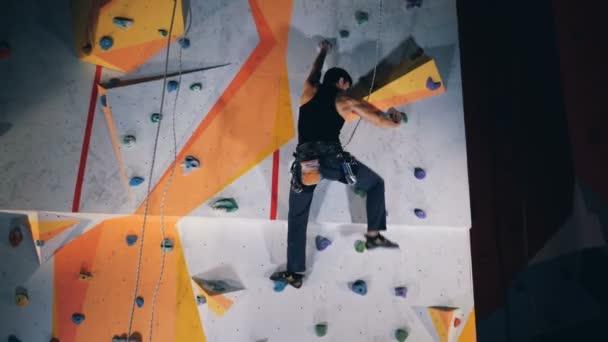 Muž horolezec na vysokou zeď, zblízka.