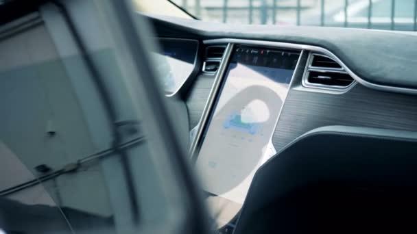 Interiér elektromobilu s jeho nabíjení zobrazen na panelu