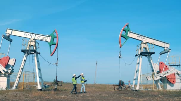 Working men check towers, pumping oil.