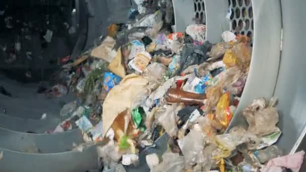 Rotating machine sorts garbage. Pile of garbage rotates at a factory for waste disposal.