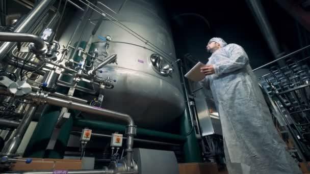 Mužské pracovník řídí fungující proces pivovarské zařízení