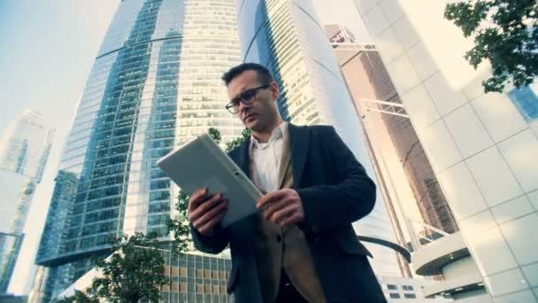Osoba pracuje s tabletem na pozadí mrakodrapů, pohled zespodu.