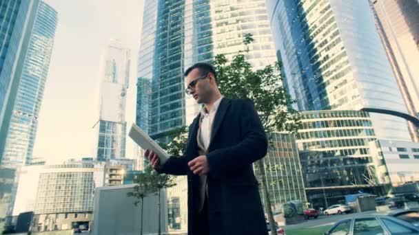 Podnikatel se dívá na tablet, stojící poblíž mrakodrapů, boční pohled.