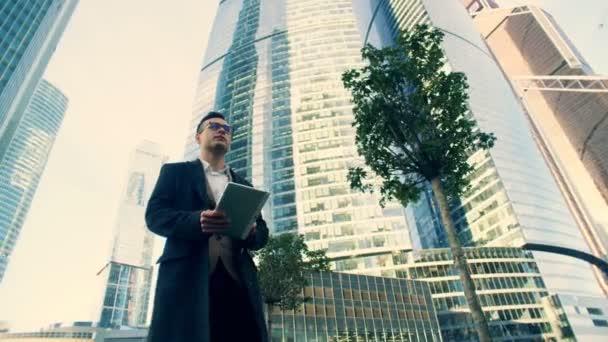 Üzletember séta-val egy tabletta közelében felhőkarcolók, közelről.