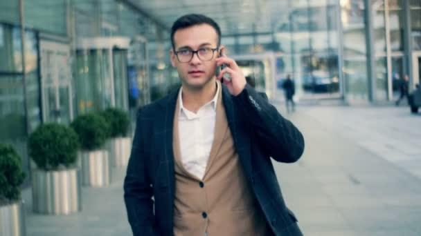 Zaneprázdněný manažer společnosti chodí na ulici, mluvit na mobilním telefonu, zblízka.