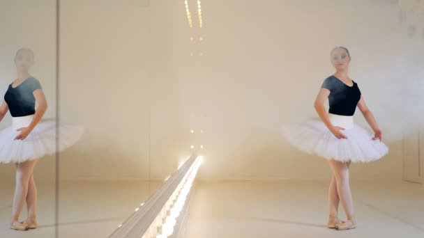 Young woman is dancing ballet in clouds of smoke near the mirror