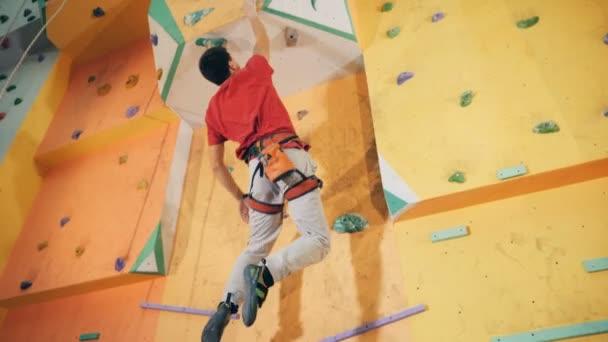 Muž horolezec je skákání a visí na stěně boulderingu. 4k