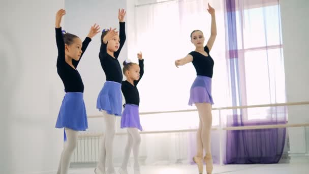 A group of little girls are learning to dance ballet with a lady teacher