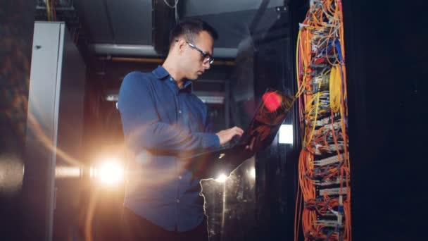 Muž drží notebook, kontrola vodičů v datovém centru, zblízka.