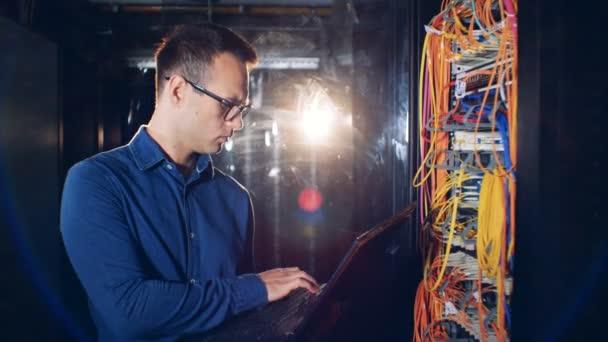 Eine Person-Typen auf einem Laptop in einem Rechenzentrum, Nahaufnahme.