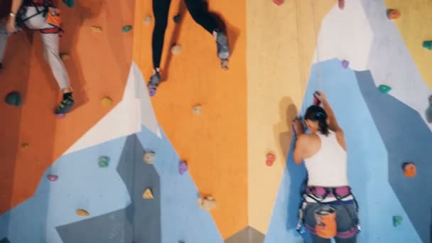 People climbing down a high wall, close up.