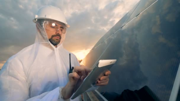 Man uses a tablet, standing near solar panels, close up.