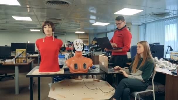 Muž a žena ovládat robota, pomocí notebooků, zblízka