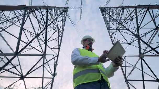 Pracovník energetika stojí mezi dvěma věžemi moci s počítačem