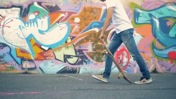 Mladý muž skočí na jeho skateboard a začne na projížďce graffiti zeď