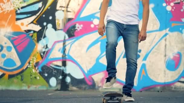 Městské graffiti zeď s mladým mužem, zvedání jeho skateboard o nohu trik