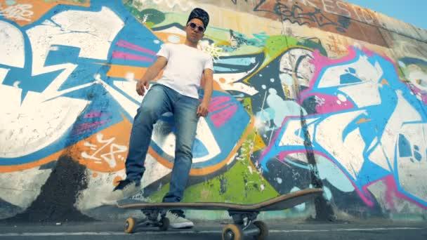 Graffiti fal és egy fiatal férfi a gördeszka, a láb emelő