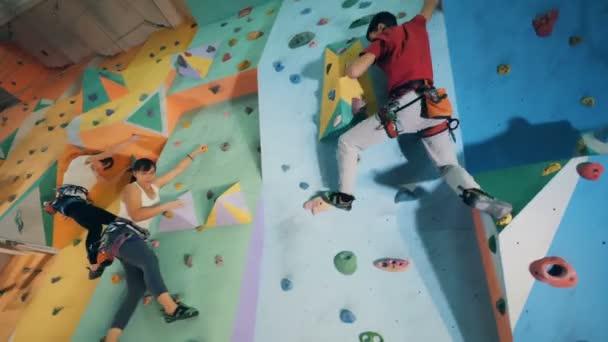 Szerzés le a fal, felnőtt hegymászók közelről.