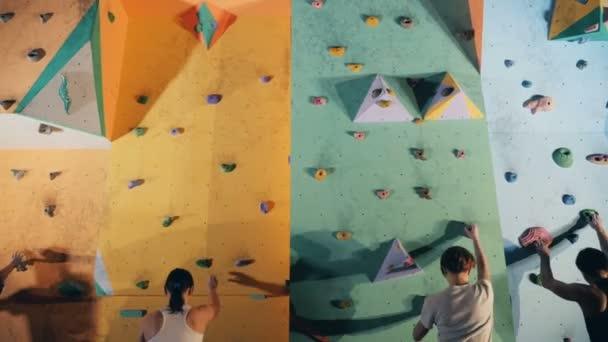 Čtyři horolezci na zdi, zblízka.