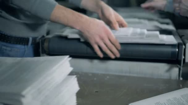 Workers piling paper on a conveyor, close up.