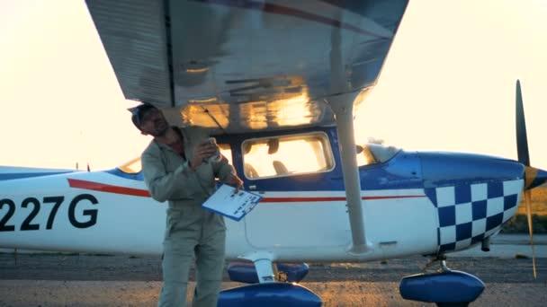Személy ellenőrzi a repülőgép szárnya, közelről.