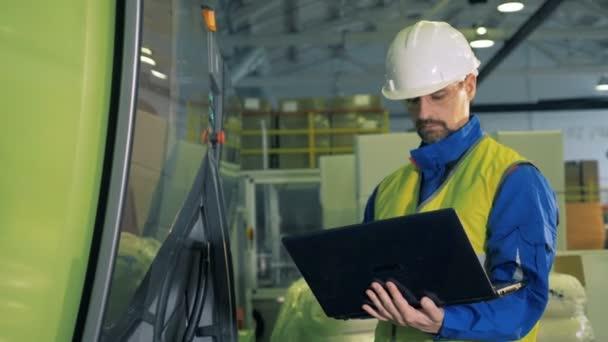 männlicher Ingenieur tippt auf einem Laptop, steht in einer Anlage, Fabrikausrüstung.