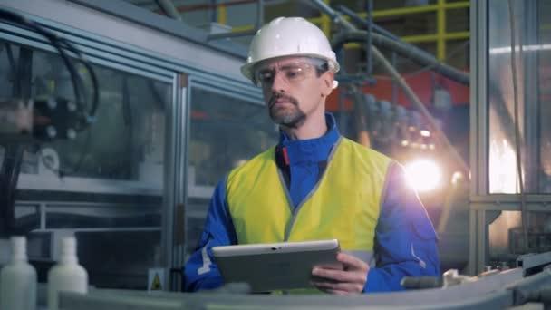 Ein Arbeiter betrachtet Flaschen, bewegt sich auf einem Förderband, tippt auf einem Tablet.