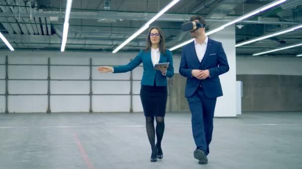 Makler und Geschäftsmann mit VR-Brille beim Gang in ein Zimmer.