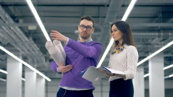 Architekten sprechen einen Plan mit Papier Schriftrollen in Händen in riesigen Büroeinrichtung