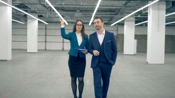Podnikatel a ženské realitní diskutovat o projektu při chůzi.