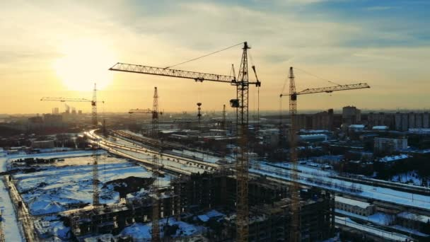 Tower cranes in work in a construction site near unfinished building.