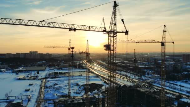 Průmyslové jeřáby pracují na staveništi venku.