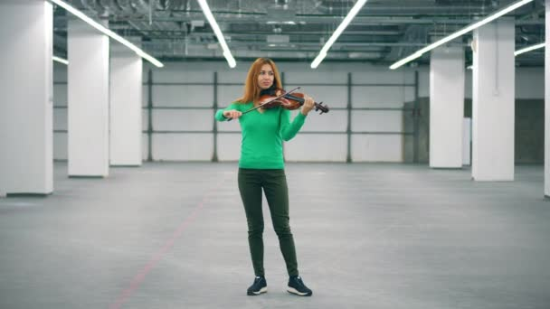A woman perform in an office room, playing violin professionally.