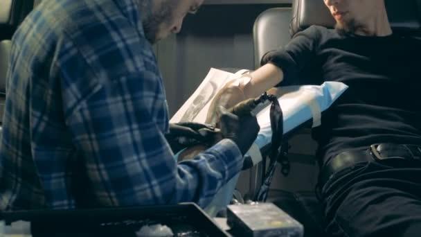 Tetovaný mistr používá zařízení při tetování ruční protézy.