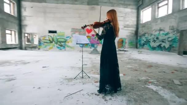 Dáma hraje na housle v prázdné budově se stěnami graffiti