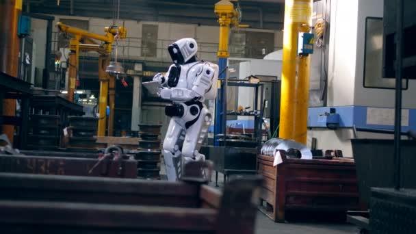 Az ember-szerű Cyborg egy tablettát használ a gyár telephelyén